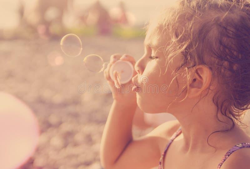 五岁的美丽的小女孩吹在sunn的肥皂泡 免版税库存照片