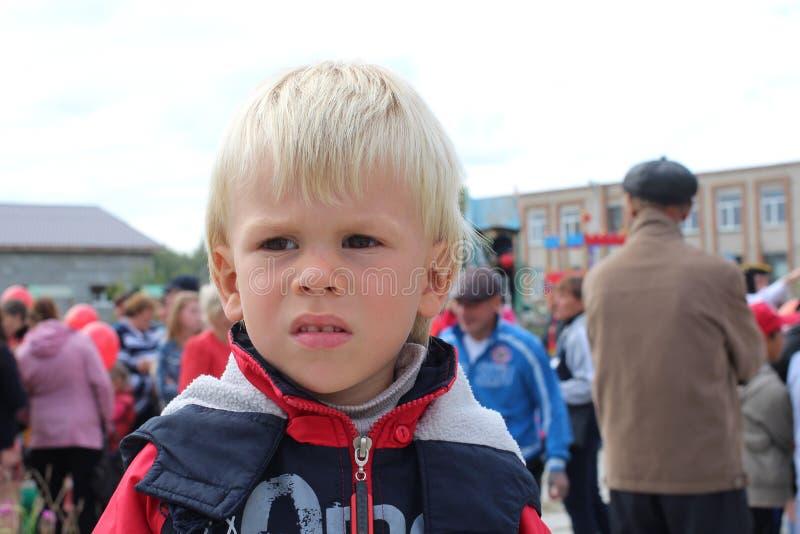 五年的小男孩孩子他从人们被触犯的阴沉的画象让步了 库存图片