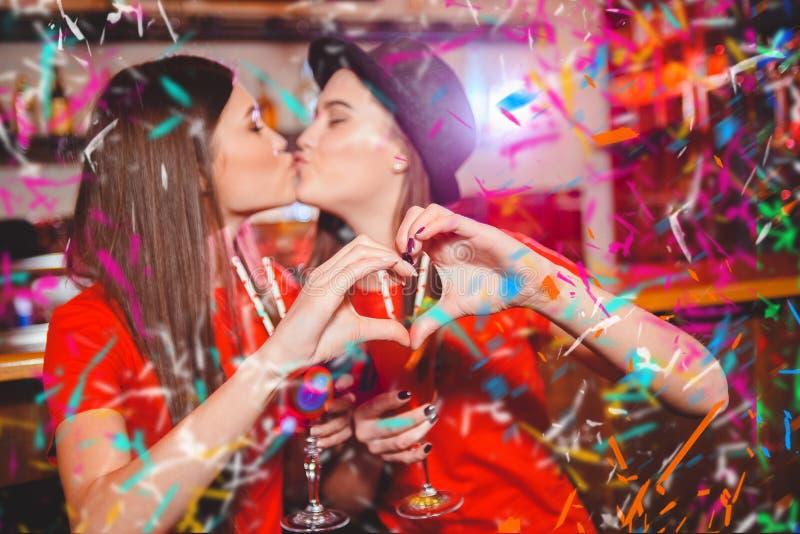 五彩纸屑党 两个年轻女同性恋的女孩亲吻和做心脏用他们的手在俱乐部党 库存图片