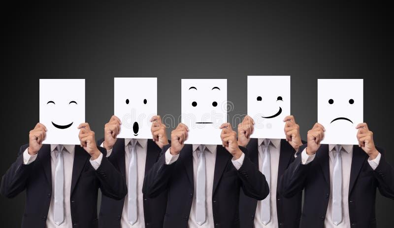 五拿着一张卡片以图画表情不同的情感感觉的商人在白皮书面对 库存照片