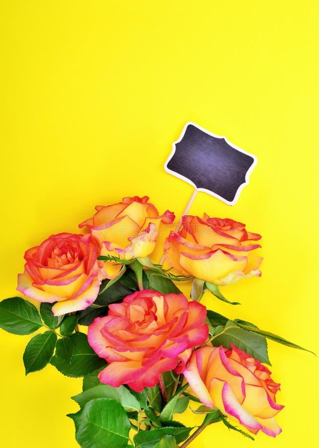 五朵玫瑰花束与一个空白的黑色的盘子的 免版税图库摄影