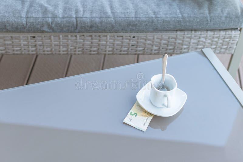 五欧元和空的咖啡在室外咖啡馆玻璃桌上的  付款,技巧 免版税库存照片