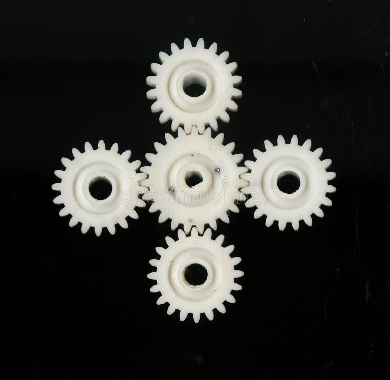五连接了不同的大小白色塑料齿状的齿轮在黑背景的 免版税库存图片