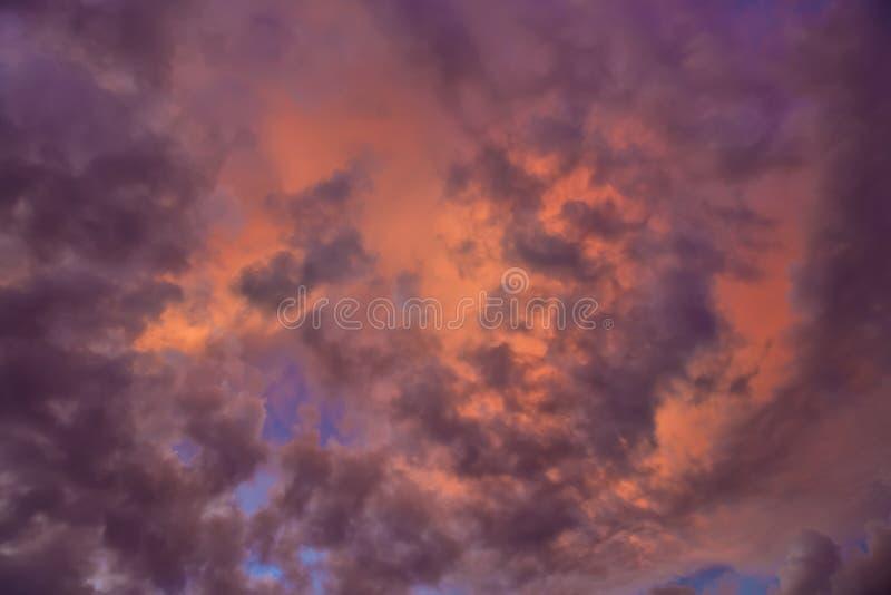 五颜六色与在云彩的红色,橙色和蓝色剧烈的天空抽象背景的 浪漫日落背景与 库存照片