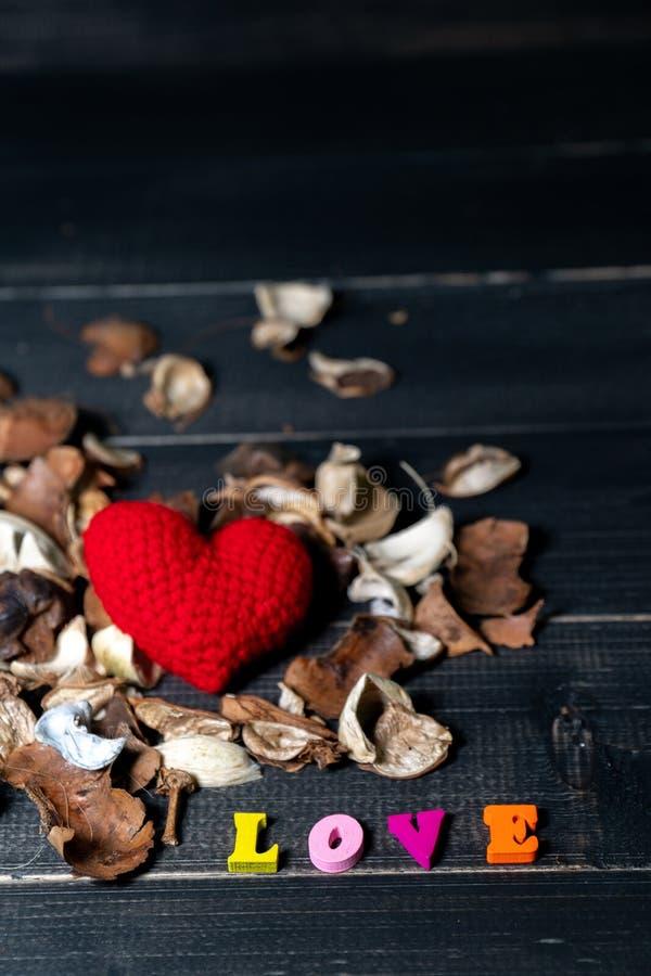 五颜六色与芳香干花和叶子的木爱文本 在干花的毛线红心在黑木桌上 库存图片