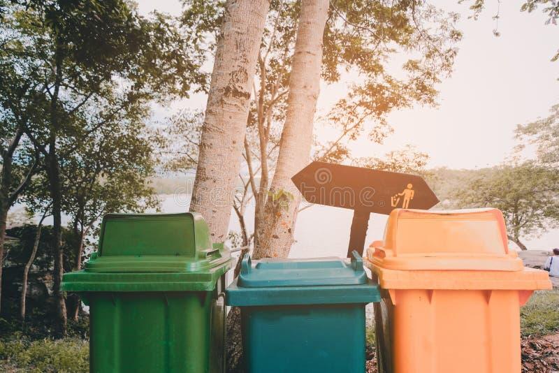 五颜六色回收站在公园为保护环境 苹果苹果概念红色行身分志愿者 图库摄影