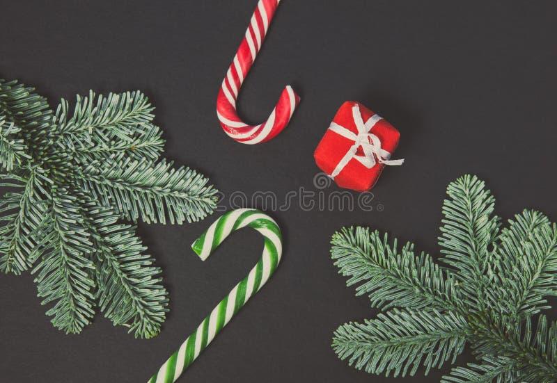 五颜六色圣诞节的糖果和在黑背景,顶视图的礼物盒 免版税库存照片