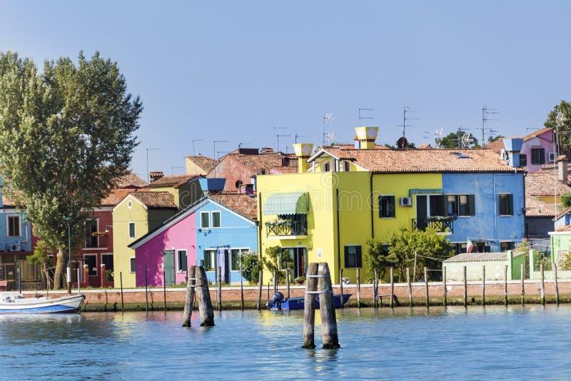 五颜六色在Burano海岛、意大利和圣马蒂诺教会的塔上的被绘的房子  库存图片