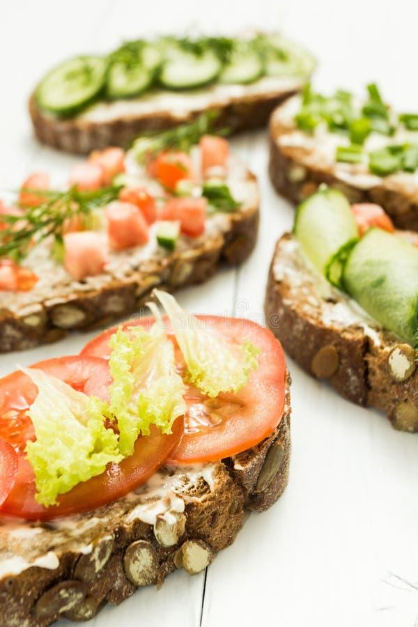 五颜六色的三明治不同形式在白色木背景的 健康生活方式和饮食 垂直 免版税库存照片