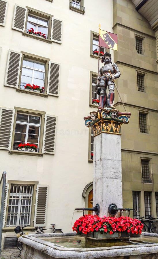 五颜六色的中世纪方旗武士雕象的美好的城市街道视图在精心制作的喷泉顶部的在伯尔尼,瑞士 库存图片