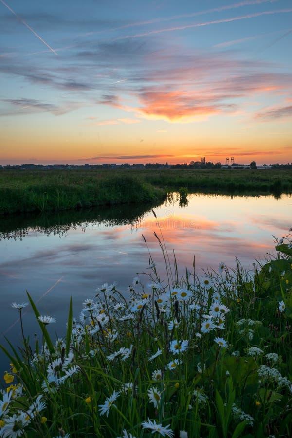 五颜六色的云彩的反射在一条运河的水中在荷兰乡下 免版税库存照片
