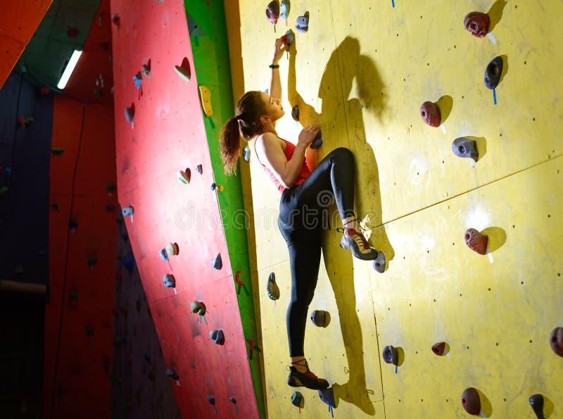 五颜六色的人为岩石的年轻活跃妇女Bouldering在上升的健身房 极限运动和室内上升的概念 免版税库存图片