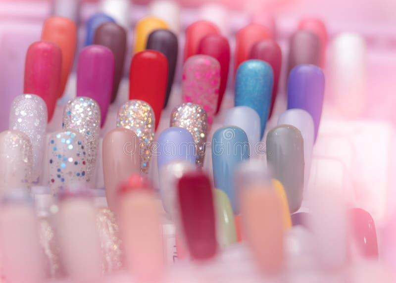 五颜六色的人为钉子在钉子沙龙商店 设置顾客的错误钉子能选择修指甲的在钉子的颜色或修脚 免版税库存图片
