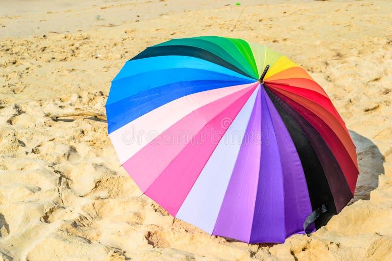 五颜六色的伞和沙子背景 免版税库存图片