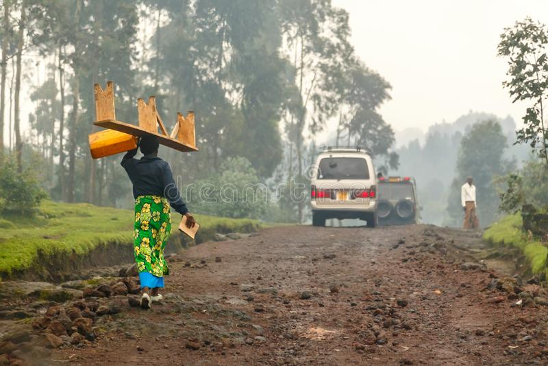 五颜六色的传统布料walikung和运载的长凳的在她的头,基加利,卢旺达卢旺达妇女 免版税库存照片