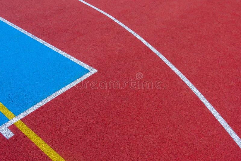 五颜六色的体育法院背景 对红色和蓝色领域橡胶地面的顶视图与户外白色和黄线 免版税图库摄影