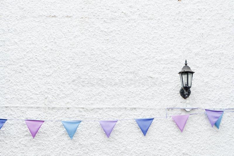 五颜六色的党下垂垂悬在与壁灯光的白色墙壁背景的旗布 最小的行家样式设计 免版税库存图片