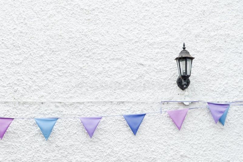 五颜六色的党下垂垂悬在与壁灯光的白色墙壁背景的旗布 最小的行家样式设计 图库摄影