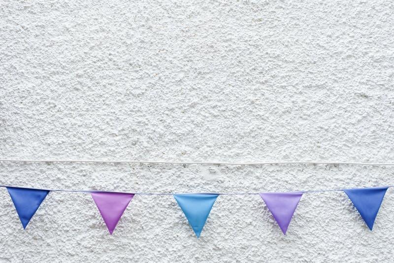 五颜六色的党下垂垂悬在白色墙壁背景的旗布 最小的行家样式设计 免版税库存照片