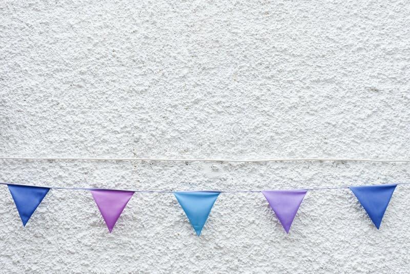五颜六色的党下垂垂悬在白色墙壁背景的旗布 最小的行家样式设计 免版税图库摄影
