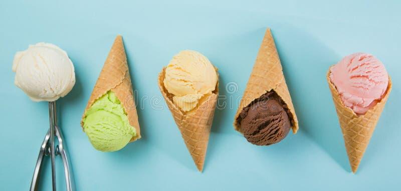 五颜六色的冰淇凌瓢的选择在蓝色背景的 免版税库存照片