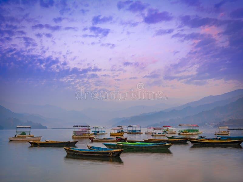 五颜六色的划艇令人惊讶的看法在日落以后的Phewa湖 免版税库存照片