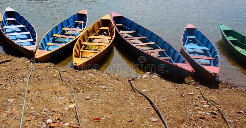 五颜六色的划艇被栓对岸在Pokhara湖,尼泊尔 免版税库存图片