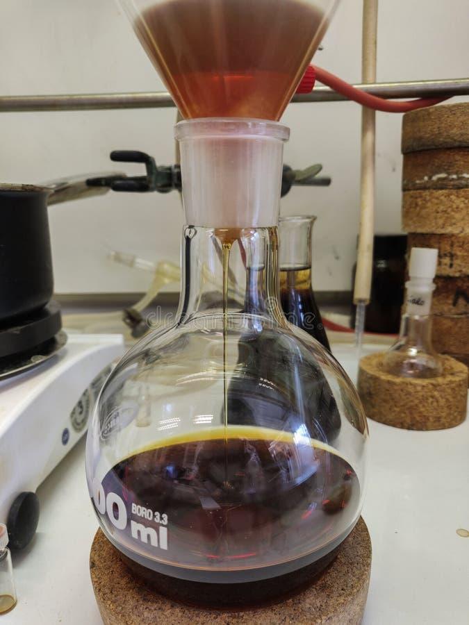 五颜六色的反应混合物滤清通过漏斗到一个圆的底下烧瓶 库存图片