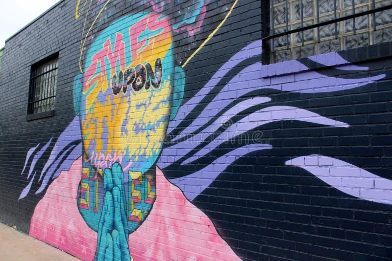 五颜六色的图美好的街道艺术在黑墙壁,街市奥斯汀,得克萨斯的,2018年 库存照片
