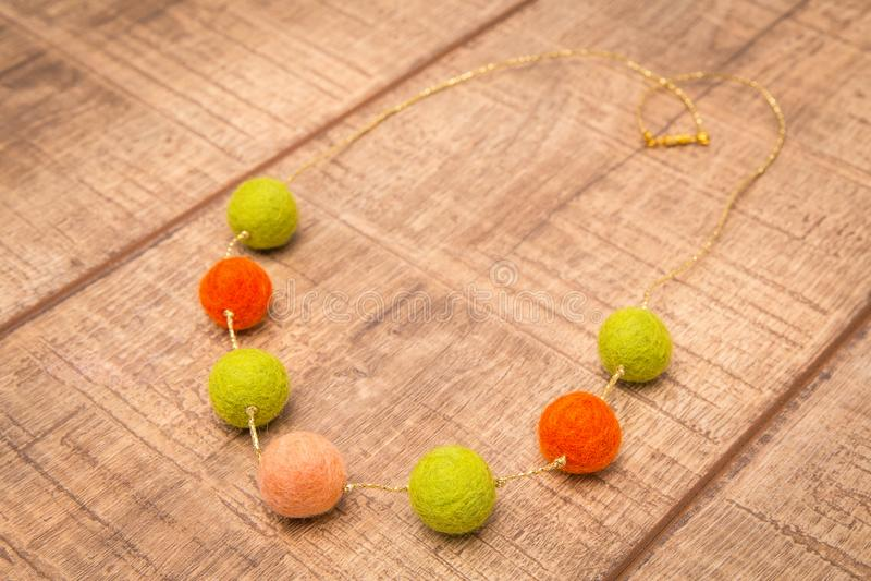 五颜六色的圆的羊毛感觉小珠项链手工制造与在木桌上的橄榄,橙色和极好的颜色小珠 免版税库存图片