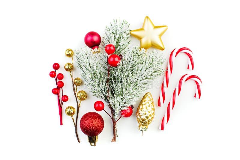 五颜六色的圣诞节decortions 红色中看不中用的物品、多雪的冬天霍莉莓果、棒棒糖和绿色冷杉分支在白色背景 库存图片