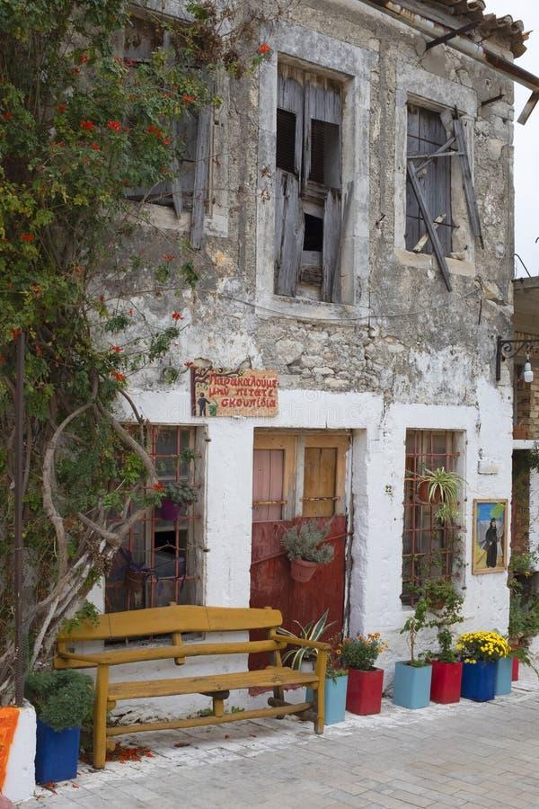 五颜六色的在遗弃大厦前面的罐树和花在Archanes,希腊 图库摄影