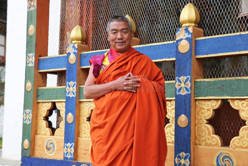 五颜六色的场面的橙色着长袍的修士姿势在不丹 免版税库存照片