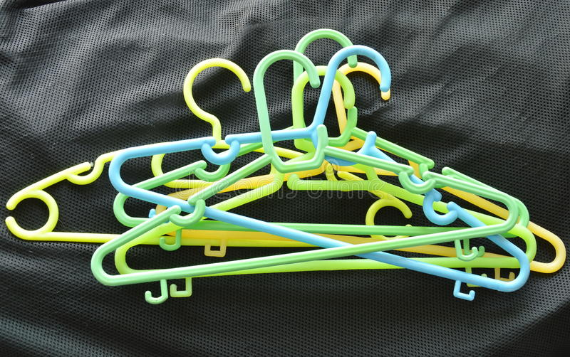 五颜六色的塑料给在黑织品的饥饿穿衣 库存图片