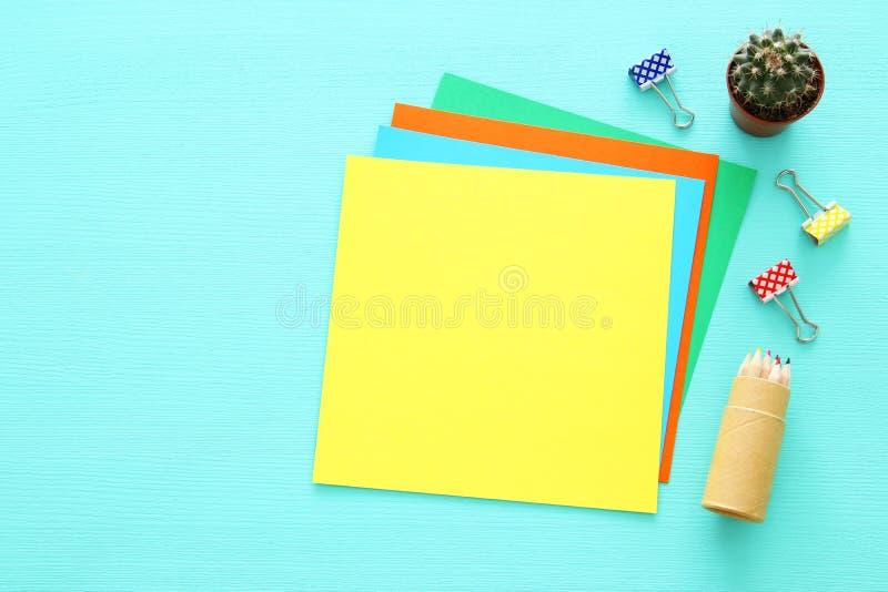 五颜六色的备忘录空的页和其他办公用品在薄荷的蓝色办公桌桌 顶视图 免版税库存图片
