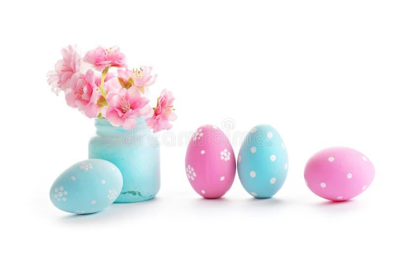 五颜六色的复活节彩蛋和在白色背景隔绝的春天花 免版税库存照片