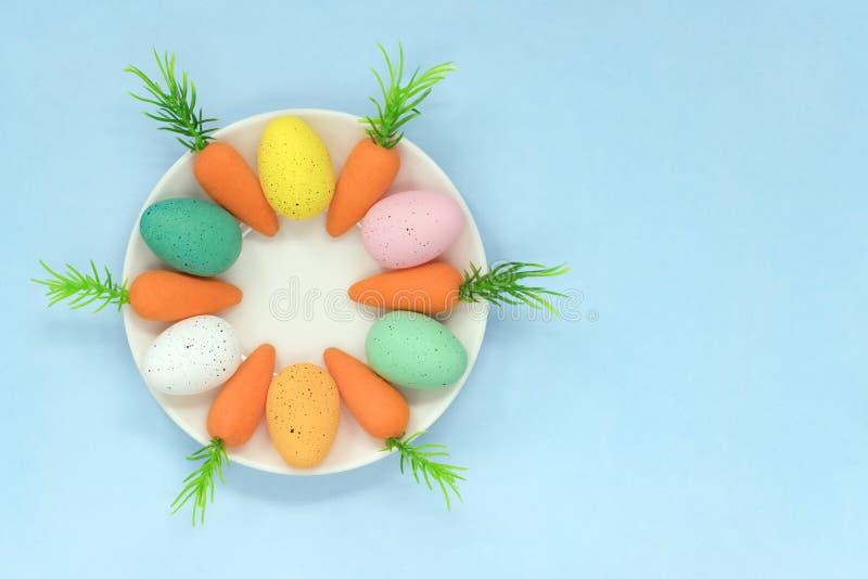 五颜六色的复活节彩蛋和红萝卜在一个茶碟,在浅兰的背景与拷贝空间 免版税库存图片