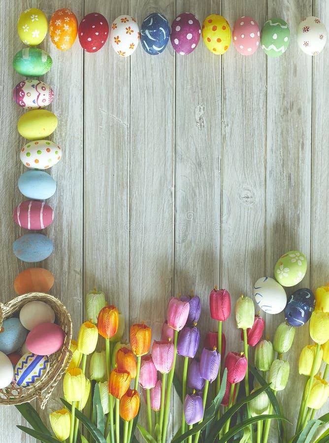 五颜六色的复活节彩蛋和郁金香在木头 库存图片