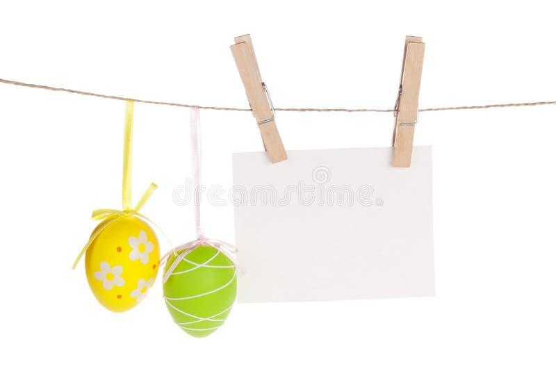 五颜六色的复活节彩蛋和空白的照片构筑垂悬在绳索 免版税库存照片