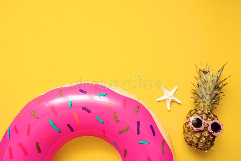 五颜六色的夏天舱内甲板放置用桃红色可膨胀的圈子多福饼、滑稽的菠萝在太阳镜和海星在黄色背景 免版税图库摄影
