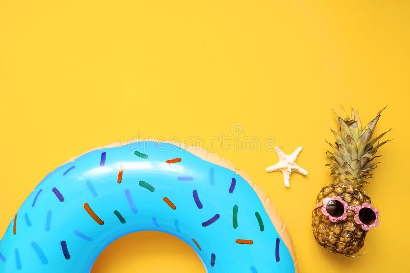 五颜六色的夏天舱内甲板放置用蓝色可膨胀的圈子多福饼、滑稽的菠萝在太阳镜和海星在黄色背景 库存图片