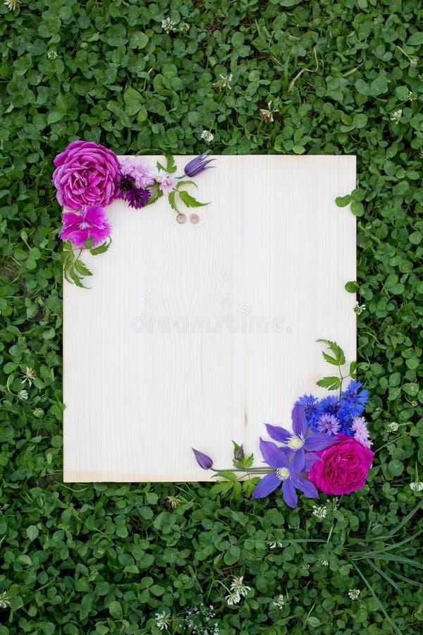 五颜六色的夏天花和木板在绿草 免版税图库摄影