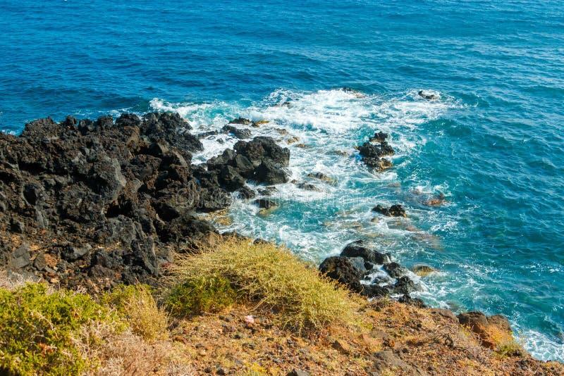 五颜六色的多岩石的海滩在圣托里尼,希腊 库存照片