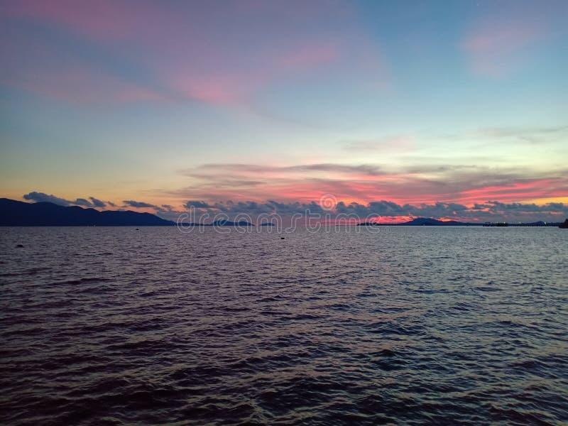 五颜六色的天空在酸值张附近的蓝色海 免版税库存图片