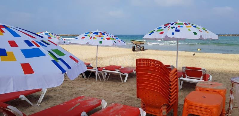 五颜六色的太阳阴影伞和橙色椅子 免版税图库摄影