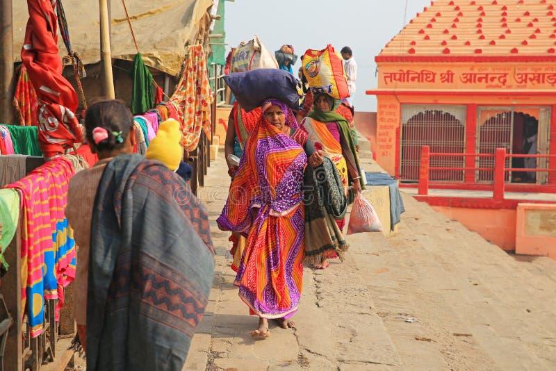五颜六色的女性香客队伍沿恒河,印度的 图库摄影