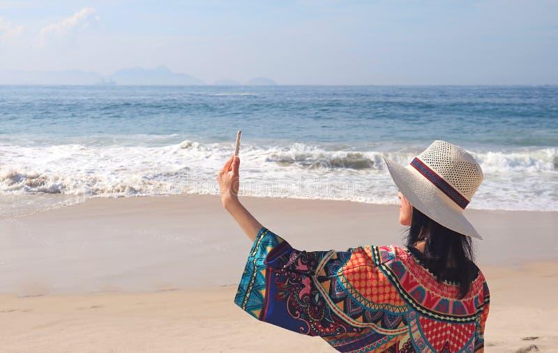 五颜六色的女衬衫的少妇喜欢拍在科帕卡巴纳海滩,里约热内卢,巴西的Selfie照片 库存照片