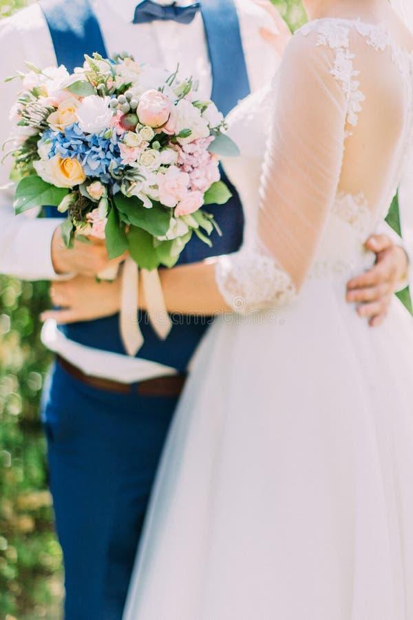五颜六色的婚礼花束的特写镜头照片在新婚佳偶的手上 图库摄影