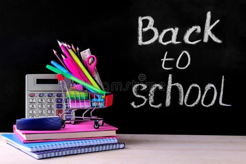 五颜六色的学校用品和购物台车在校务委员会的背景与词回到学校 免版税库存照片