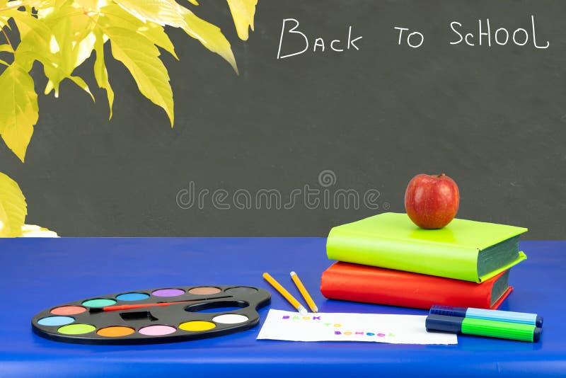 五颜六色的学校设备和两本书在再深蓝桌上 免版税库存照片